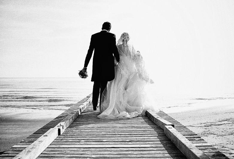 Servizio fotografico di matrimonio in stile reportage. Sposi su camminano su una passerella. Il Blog di Michelino Studio, Fotografo di matrimonio in Veneto.